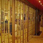 A Vision Guard sliding folding shutter in a gold finish installed at an international cruise ship.